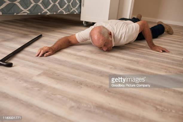 homme aîné sur le plancher dans la douleur après une chute - lying down photos et images de collection
