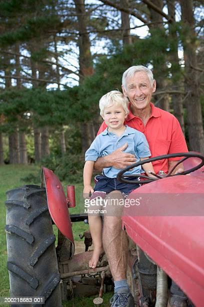Senior man on tractor with grandson (2-4), portrait