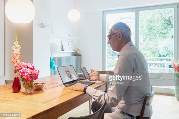 senior man on video call to doctor discussing blood test results on smart phone - mindzoom 2 stock pictures, royalty-free photos & images