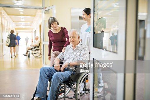 Senior man on wheelchair with wife and nurse