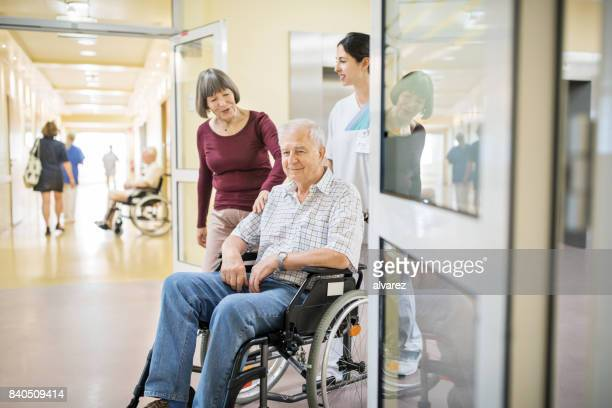 Senior man on wheelchair with wife and nurse