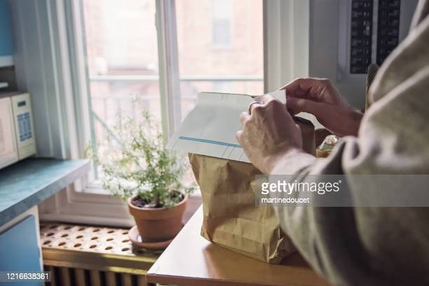 """senior man opening bag of delivered food on counter. - """"martine doucet"""" or martinedoucet stock pictures, royalty-free photos & images"""