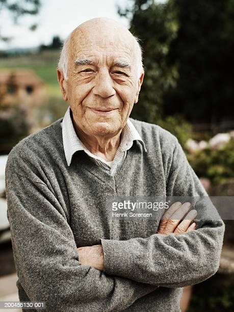 Senior man outdoors, arms folded, close-up, portrait