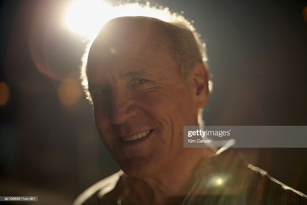 Senior man outdoors at night, backlit by source of light, portrait, close-up (lens flare) : Stock Photo