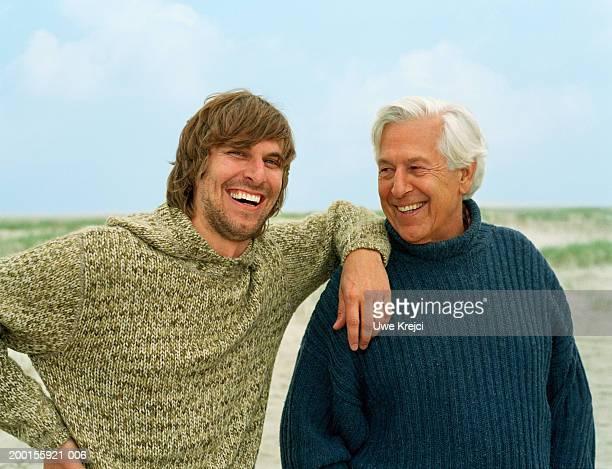 senior man outdoors with adult son, smiling, portrait of son - côte à côte photos et images de collection