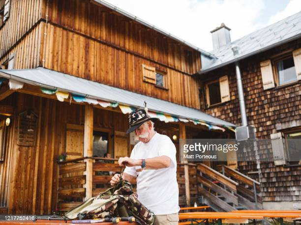 senior man packing outside mountain cabin - austria stock pictures, royalty-free photos & images