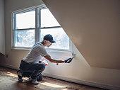 Senior man painting apartment interior