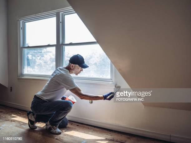 senior man painting apartment interior - dipinto foto e immagini stock