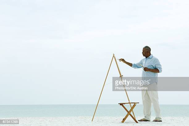 Senior man painting canvas beach, side view
