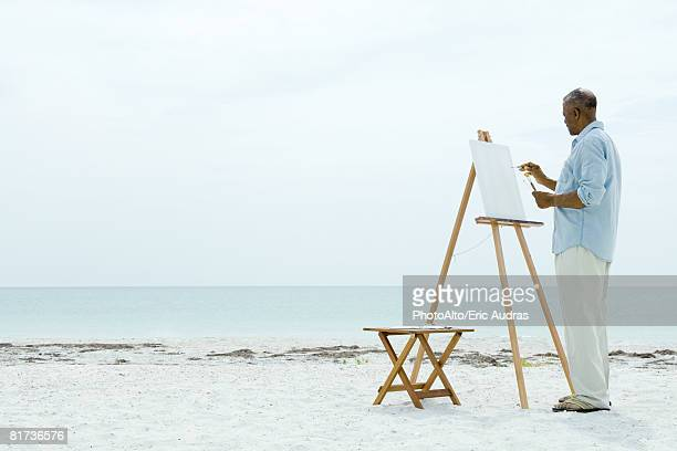 Senior man painting on canvas at the beach, side view