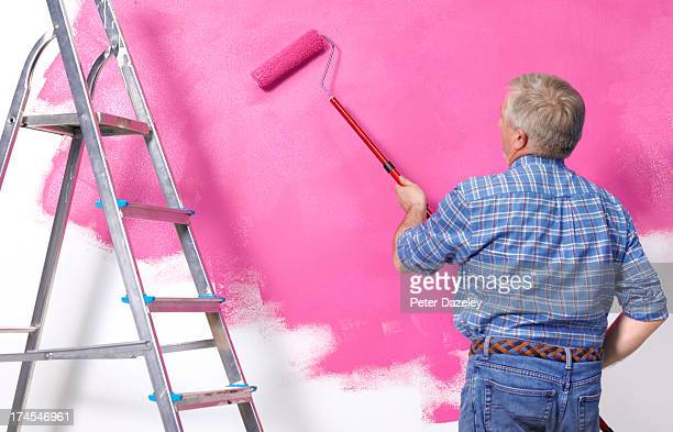 Senior man painting wall in new home