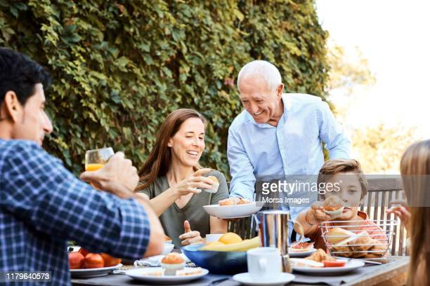 senior man passing muffins to family in backyard - serving food and drinks stock pictures, royalty-free photos & images