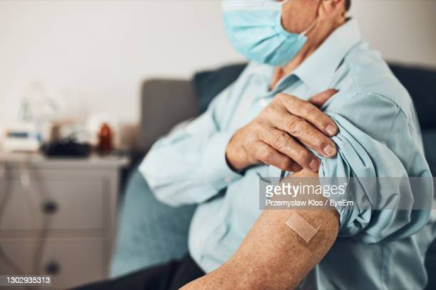 senior man patient holding shirt sleeve up with a plaster in place of injection of vaccine. covid-19 - arm stock pictures, royalty-free photos & images