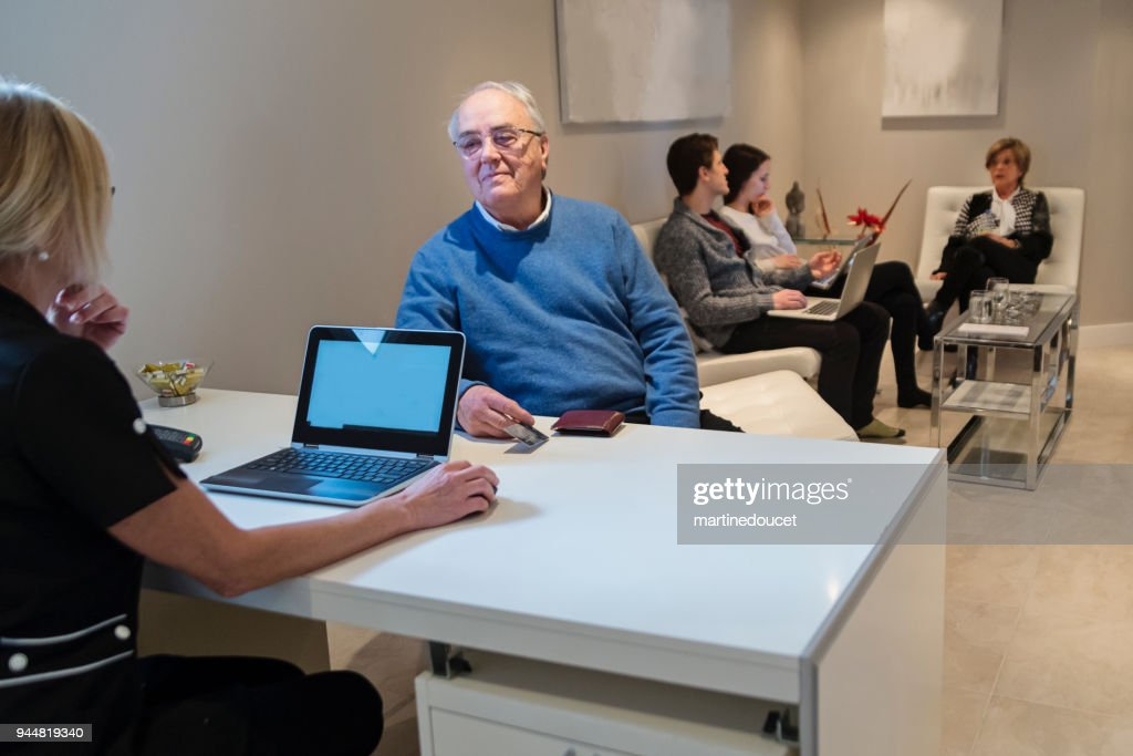 Senior man paying a consultation in clinic. : Stock Photo