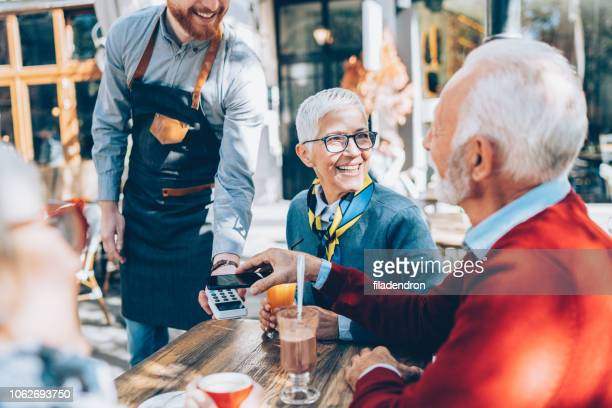 senior man paying contactless with smartphone
