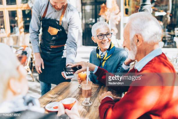 senior man paying contactless with smartphone - money transfer stock pictures, royalty-free photos & images