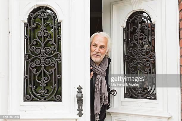 Senior man peeking through doorway