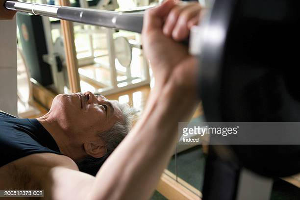 Senior man performing bench press in gym, elevated view
