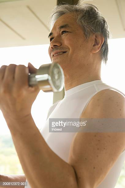 Senior man performing dumbbell curl, smiling, low angle view