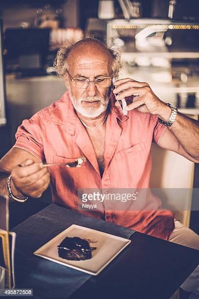 """Alter Mann telefonisch und Essen Kuchen in der Patisserie """"Homage"""""""