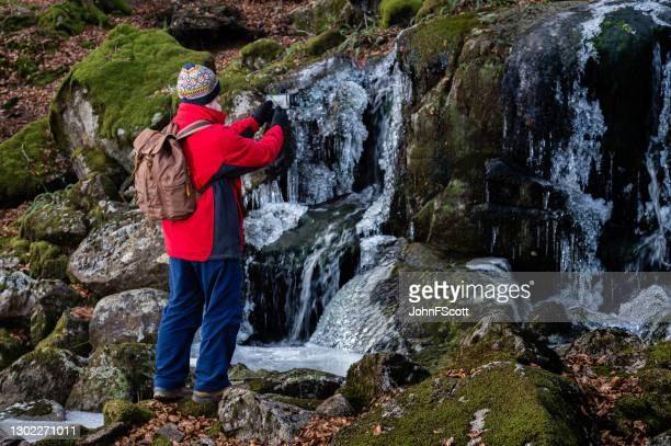 senior man photographing a frozen waterfall - johnfscott stock pictures, royalty-free photos & images