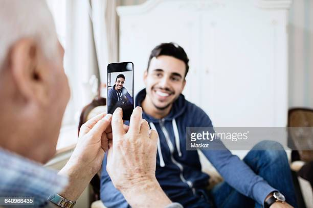 Senior man photographing caretaker through smart phone