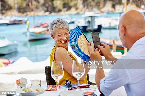 Senior man photographing woman holding hand fan