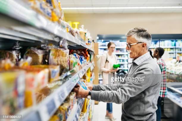 senior man picking out bread at supermarket - einzelner senior stock-fotos und bilder