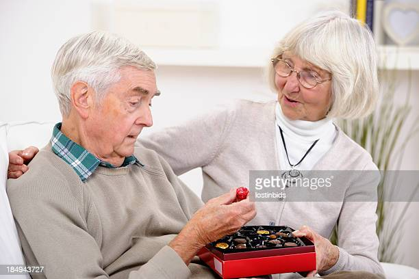 senior man picking out chocolate from a box - couple chocolate stock pictures, royalty-free photos & images