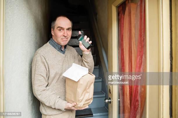 """senior mann abholen kontaktlos geliefertes essen vor der haustür. - """"martine doucet"""" or martinedoucet stock-fotos und bilder"""