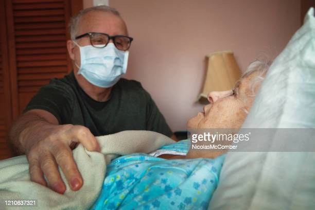 senior man places blanket on his sick female partner - death stock pictures, royalty-free photos & images