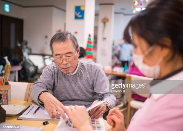 Senior man planning to draw picture with female nurse