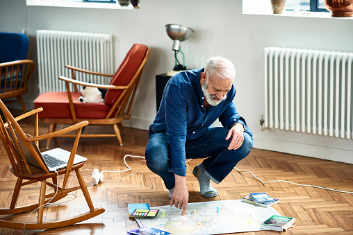 Senior man planning vacation with sticky notes on map - gettyimageskorea