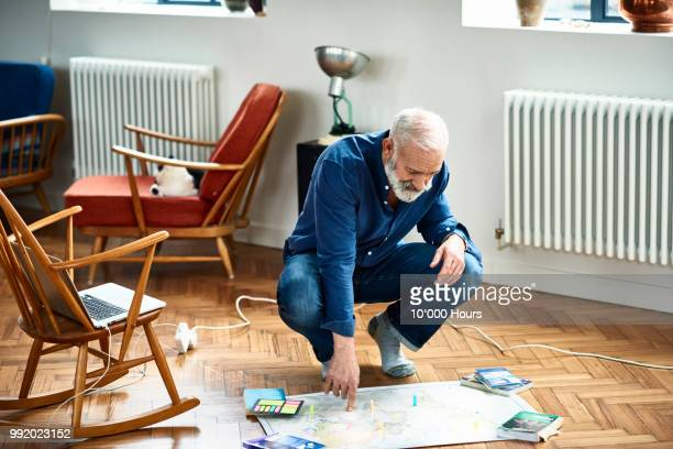 Senior man planning vacation with sticky notes on map