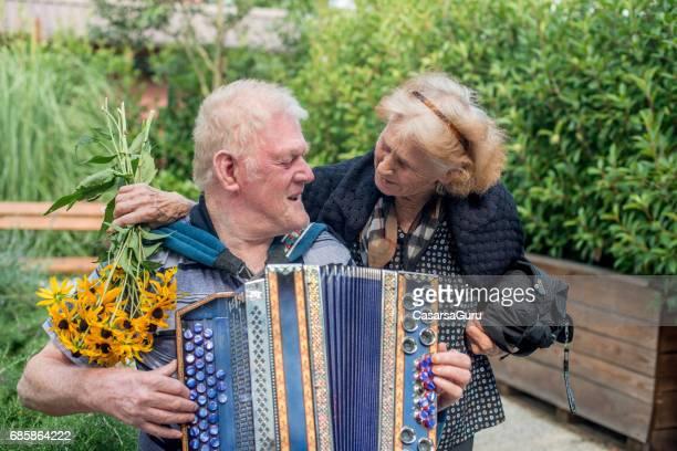 Senior Man Playing Accordation At The Backyard Of The Nursing Home