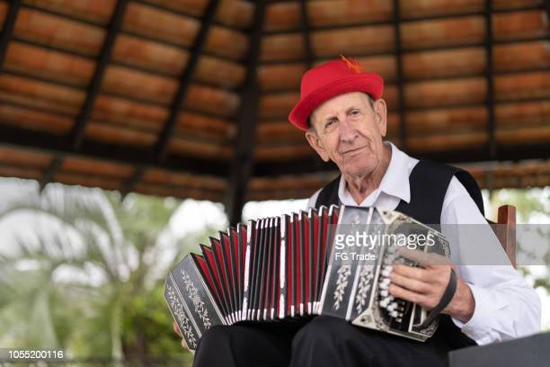 senior man playing accordion - porto alegre stock pictures, royalty-free photos & images