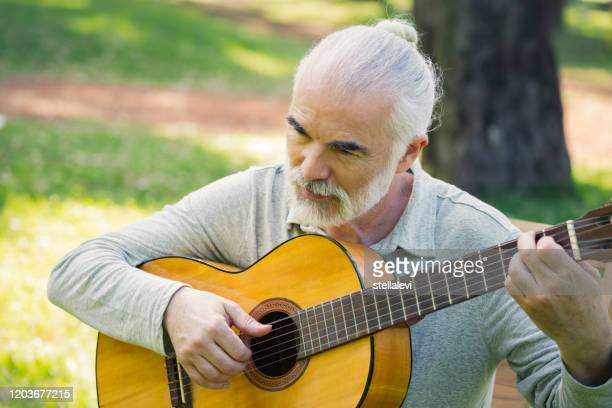 senior man playing acoustic guitar in the park - stellalevi stock pictures, royalty-free photos & images