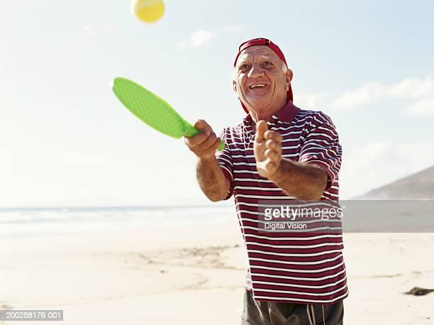 Senior man playing beach tennis, smiling