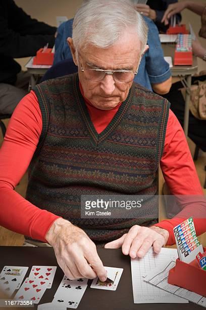 senior man playing bridge. - bridge card game stock-fotos und bilder