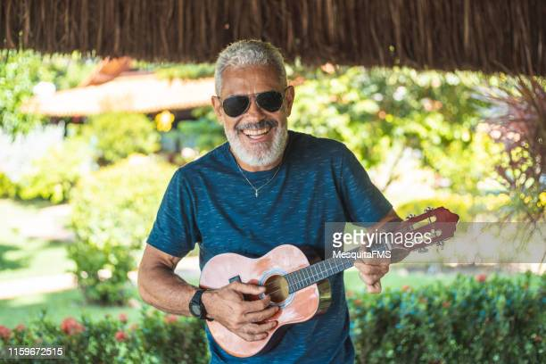 senior man playing cavaquinho - plucking an instrument stock pictures, royalty-free photos & images
