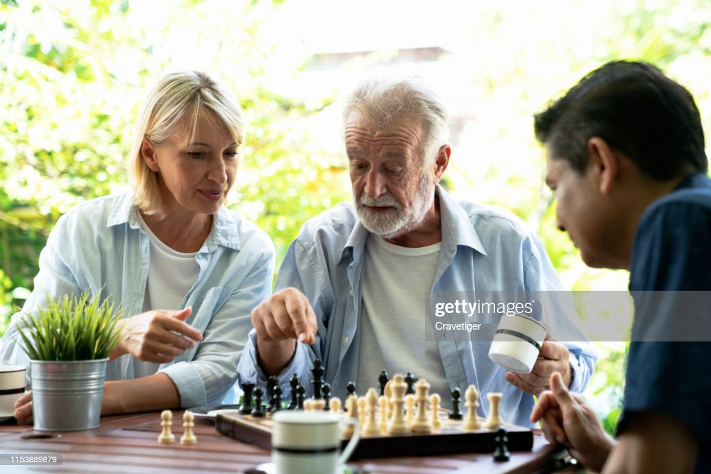 Senior man playing chess and thinking about the game with her woman help with young man . He 's preparing to move chess figurine. : Stock Photo