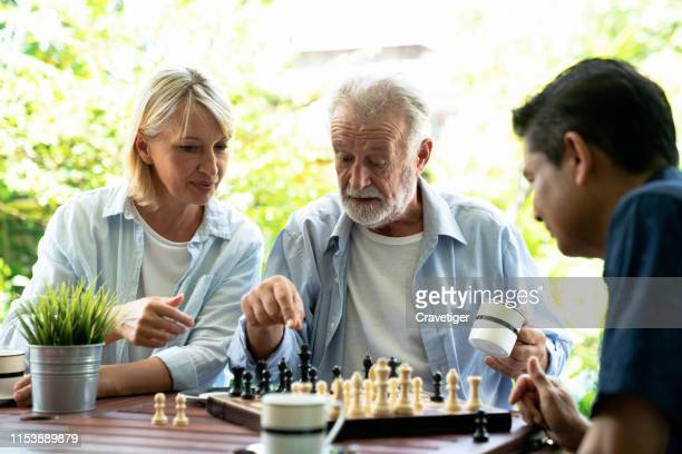 senior man playing chess and thinking about the game with her woman help with young man . he 's preparing to move chess figurine. - アルツハイマー病 ストックフォトと画像