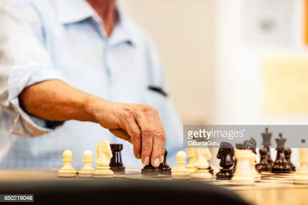 Senior Man Playing Chess At The Community Center