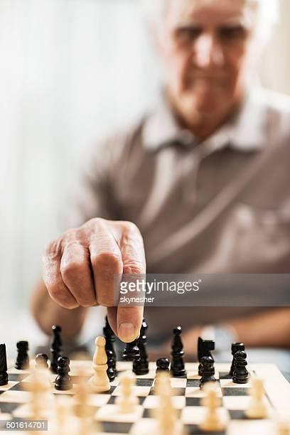 Senior man playing chess.