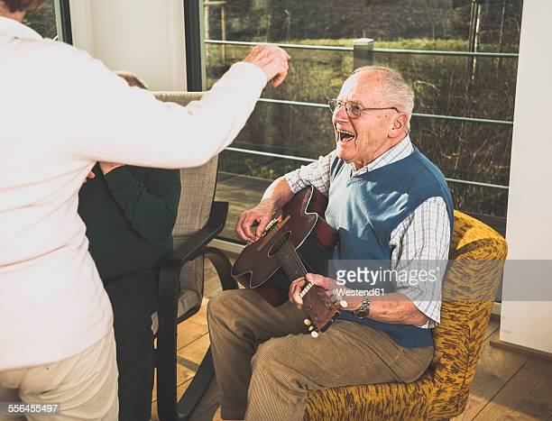 Senior man playing guitar for senior couple dancing