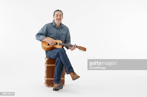 Senior man playing guitar, sitting on suitcase, stduio shot