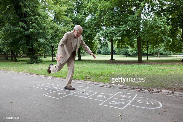 senior man playing hopscotch in the park - young at heart stock pictures, royalty-free photos & images