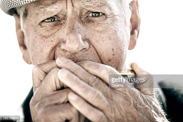 Senior man playing on harmonica