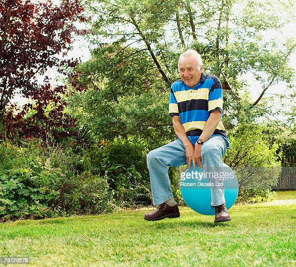 Senior man playing on inflatable hopper in garden, smiling
