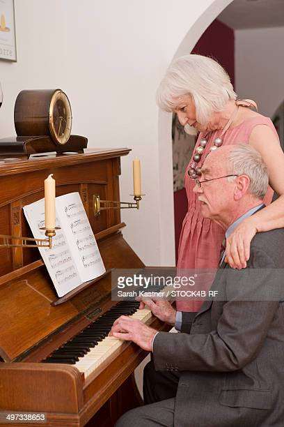 Senior man playing piano for wife
